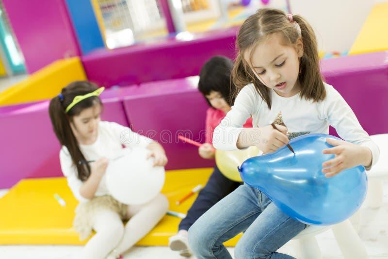 Πολυφυλετικά κορίτσια liitle στο χώρο για παιχνίδη στοκ εικόνα