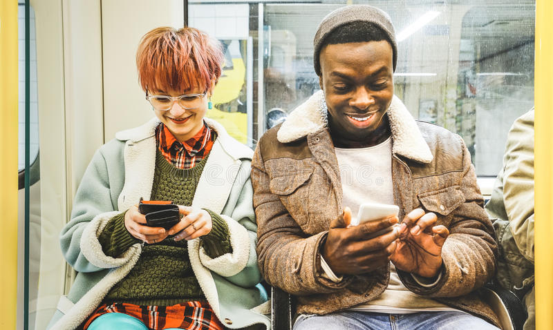 Πολυφυλετικό ζεύγος φίλων hipster που έχει τη διασκέδαση με το τηλέφωνο στοκ φωτογραφίες με δικαίωμα ελεύθερης χρήσης
