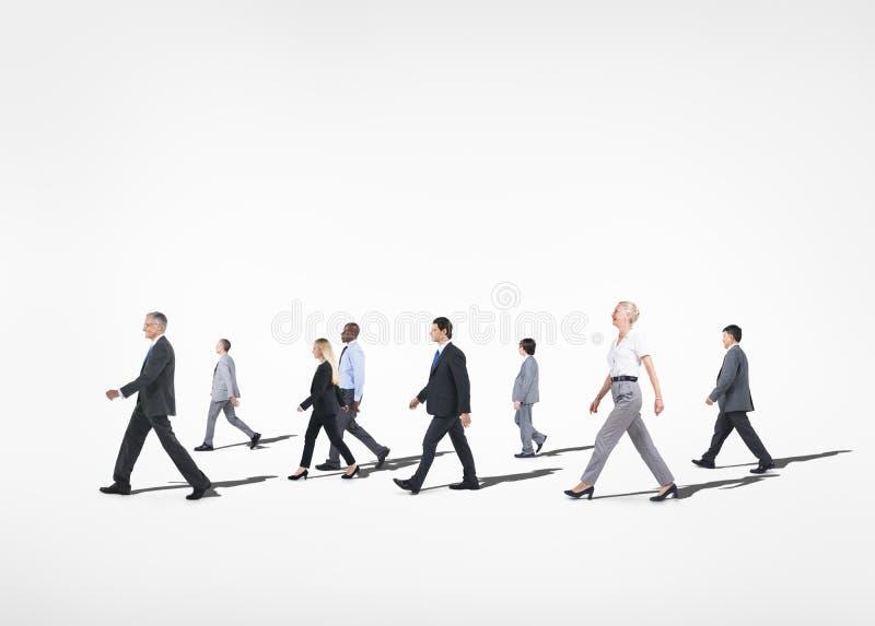 Πολυ-εθνικοί άνθρωποι που περπατούν στο άσπρο υπόβαθρο στοκ εικόνες