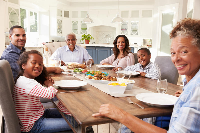 Πολυ οικογένεια μαύρων παραγωγής στον πίνακα κουζινών για ένα γεύμα στοκ εικόνα