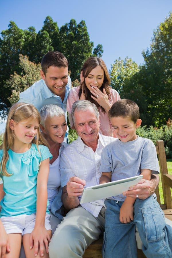 Πολυ οικογένεια παραγωγής με μια συνεδρίαση PC ταμπλετών στο πάρκο στοκ φωτογραφία με δικαίωμα ελεύθερης χρήσης