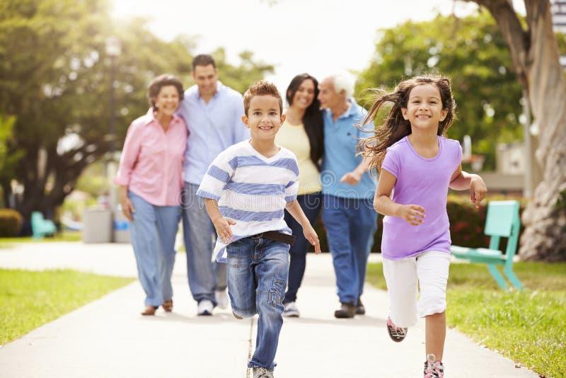 Πολυ οικογένεια παραγωγής που περπατά στο πάρκο από κοινού στοκ εικόνες