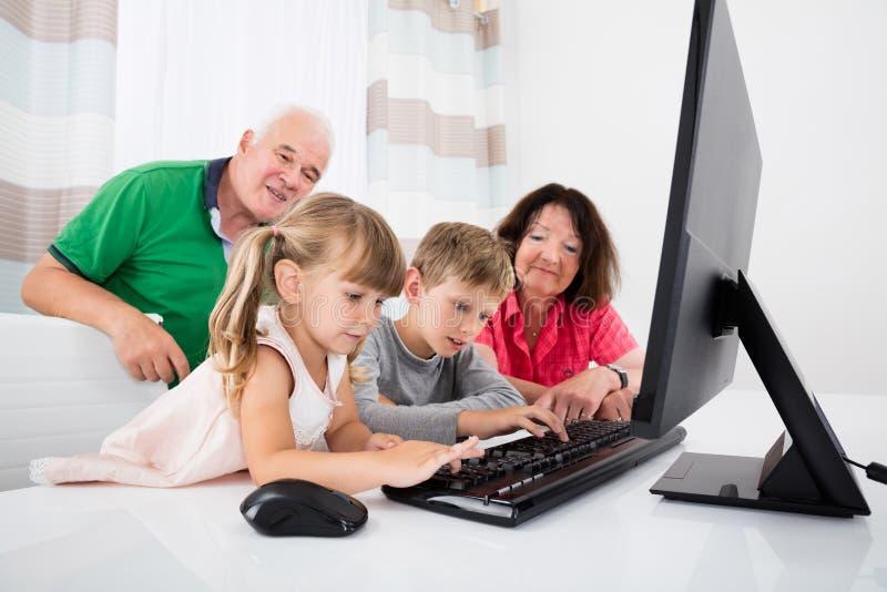 Πολυ οικογένεια παραγωγής που χρησιμοποιεί τον υπολογιστή γραφείου στο σπίτι στοκ φωτογραφίες με δικαίωμα ελεύθερης χρήσης