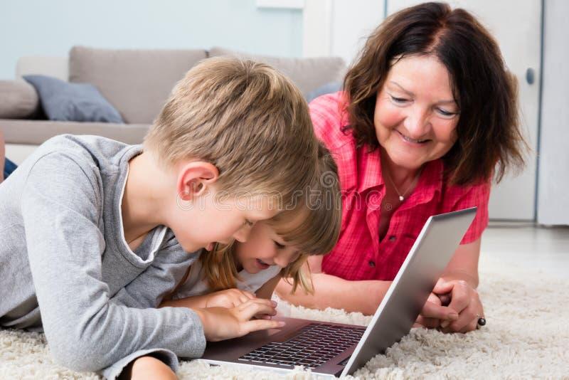 Πολυ οικογένεια παραγωγής που χρησιμοποιεί το lap-top στο σπίτι στοκ εικόνα