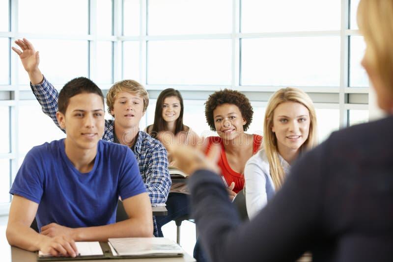 Πολυ φυλετικοί εφηβικοί μαθητές στην κατηγορία μια με το χέρι επάνω στοκ εικόνες