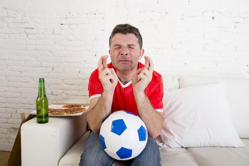Ποδόσφαιρο προσοχής ατόμων στη TV νευρική και συγκινημένη υφισμένος την πίεση που διασχίζει τα δάχτυλα για το στόχο στοκ φωτογραφία