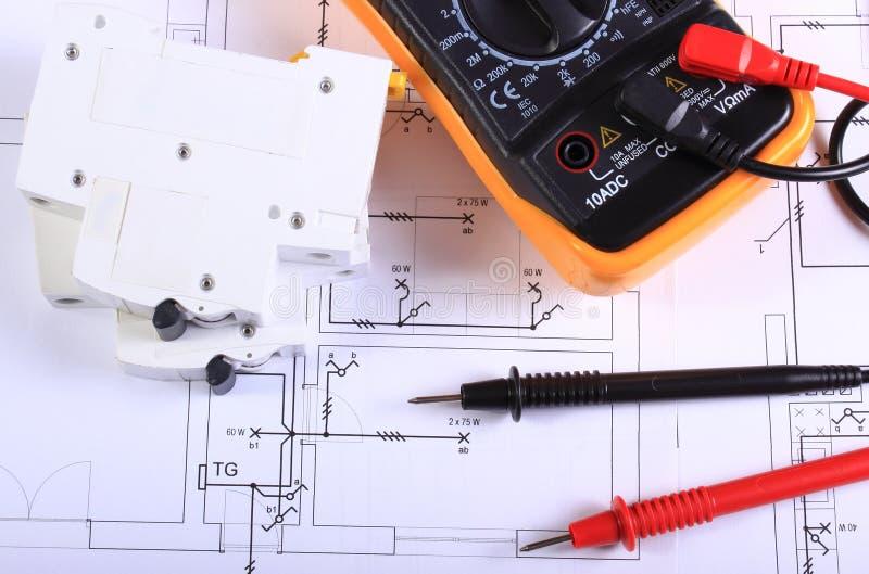 Πολύμετρο και ηλεκτρική θρυαλλίδα στο κατασκευαστικό σχέδιο στοκ εικόνα