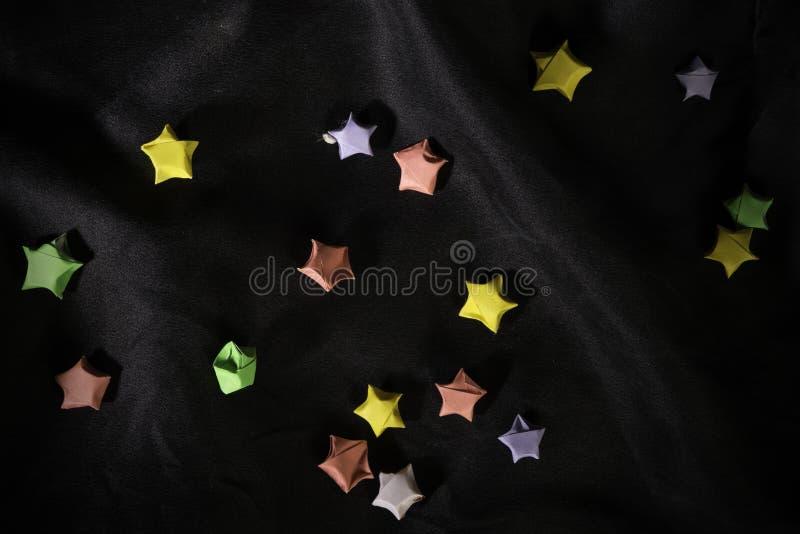 Πολύχρωμα αστέρια origami στο πίσω σατέν στοκ φωτογραφία