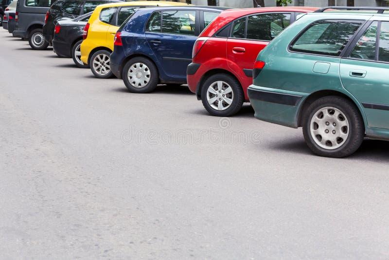Πολύχρωμα αυτοκίνητα που σταθμεύουν διαγώνια στο χώρο στάθμευσης στην οδό στοκ εικόνα με δικαίωμα ελεύθερης χρήσης