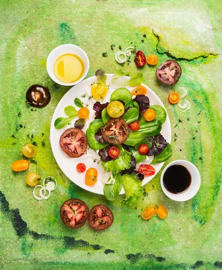 Πολύχρωμη σαλάτα ντοματών με τον επίδεσμο του ελαίου και του ξιδιού στο πράσινο υπόβαθρο στοκ φωτογραφία με δικαίωμα ελεύθερης χρήσης