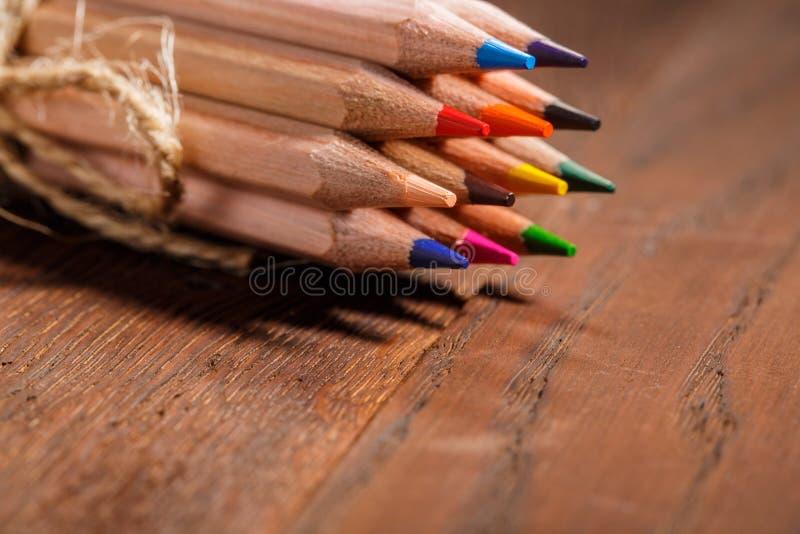 Πολύχρωμο διακοσμητικό σχοινί pensils που δένεται σε έναν ξύλινο πίνακα πίσω σχολείο διάστημα αντιγράφων στοκ φωτογραφίες με δικαίωμα ελεύθερης χρήσης