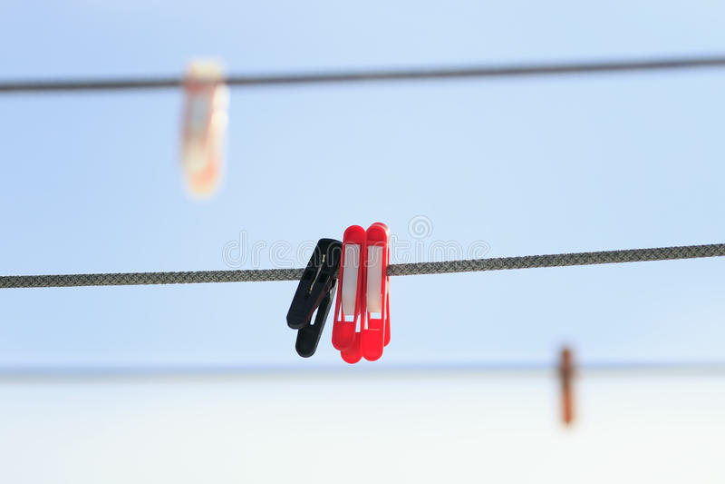 Πολύχρωμο πλαστικό clothespins που κρεμά στη σκοινί για άπλωμα επάνω στοκ εικόνες με δικαίωμα ελεύθερης χρήσης