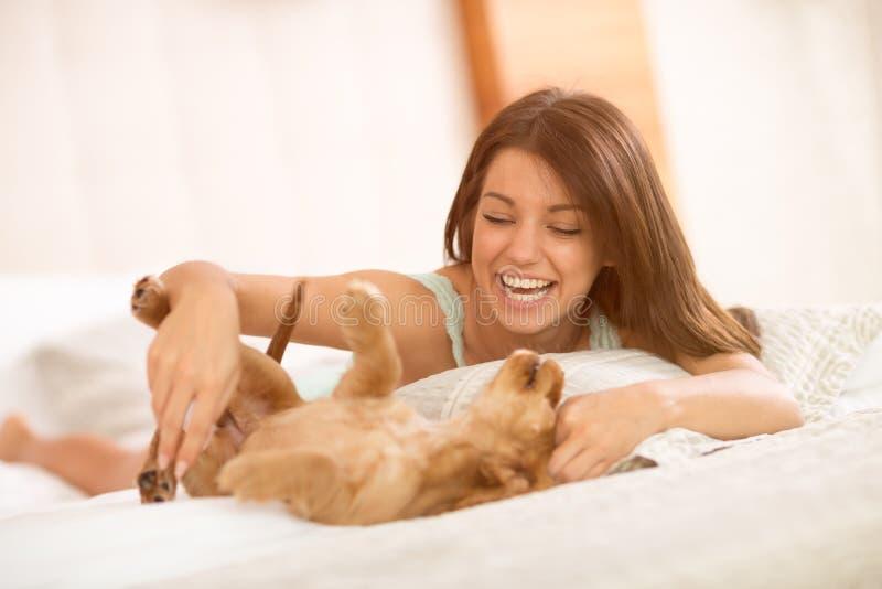 Πολύ ευτυχές παιχνίδι brunette με το κατοικίδιο ζώο κουταβιών της στοκ φωτογραφία με δικαίωμα ελεύθερης χρήσης