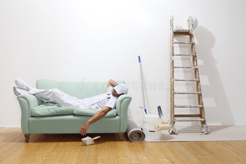 Πολύ κουρασμένη έννοια εργαζομένων, ύπνοι ατόμων ζωγράφων στον καναπέ στοκ φωτογραφία