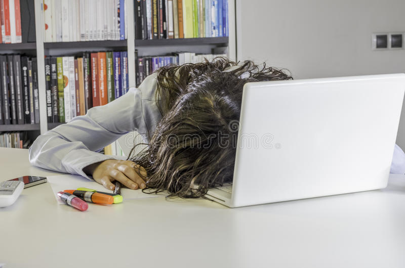 Πολύ κουρασμένη επιχειρηματίας το πρόσωπό της στο πληκτρολόγιο του lap-top στοκ εικόνες με δικαίωμα ελεύθερης χρήσης