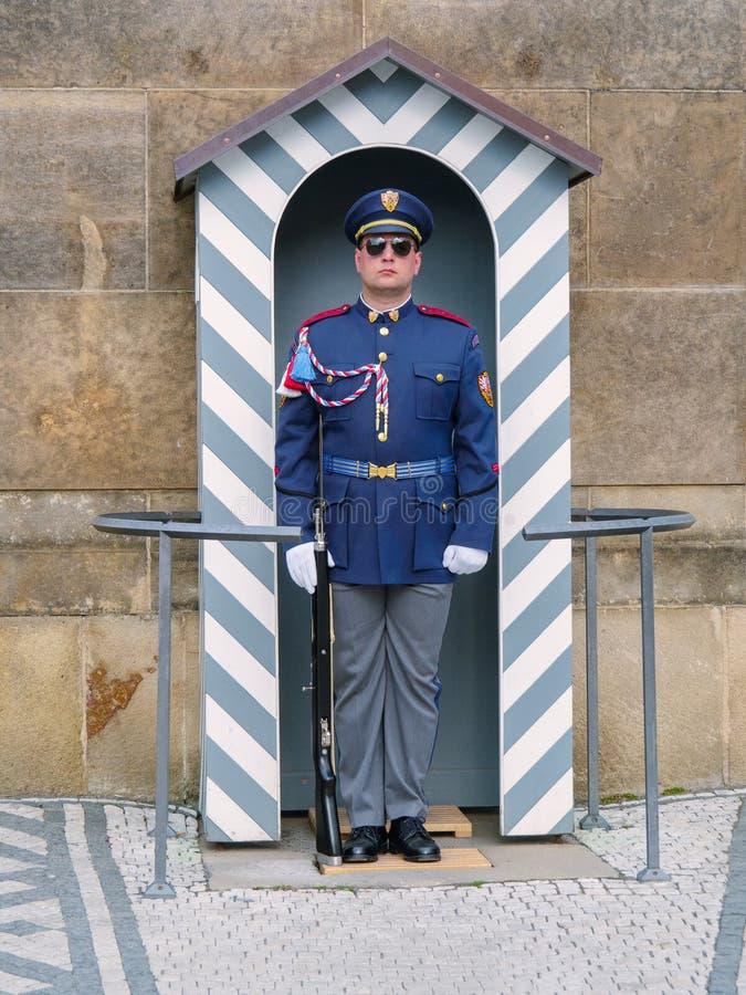 Πράγα, Τσεχία - τον Απρίλιο του 2019: Φύλακας με το τουφέκι στο καθήκον στο Κάστρο της Πράγας Άτομο μπλε σε ομοιόμορφο με τη στάσ στοκ εικόνα