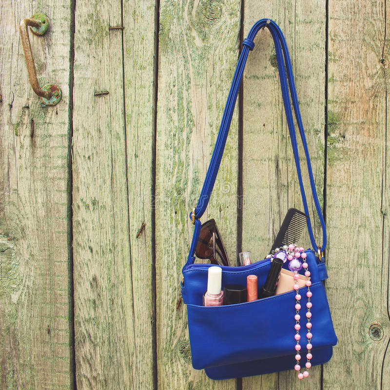 Πράγματα από το ανοικτό γυναικείο πορτοφόλι Τα καλλυντικά και τα εξαρτήματα γυναικών ` s έπεσαν από την μπλε τσάντα στοκ εικόνες