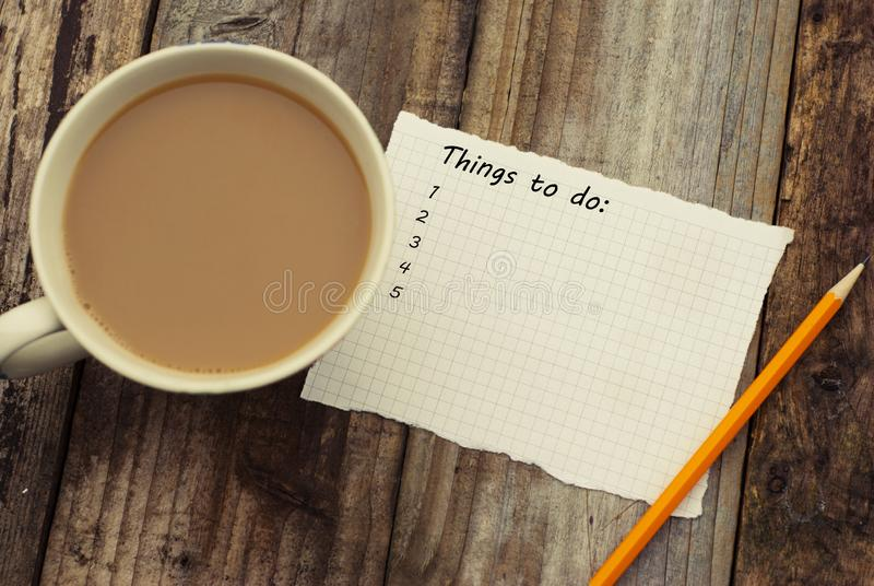 Πράγματα για να κάνει τον κατάλογο, επιγραφή Κενό papper και φλιτζάνι του καφέ, πέρα από το αγροτικό ξύλινο υπόβαθρο, εννοιολογικ στοκ φωτογραφίες