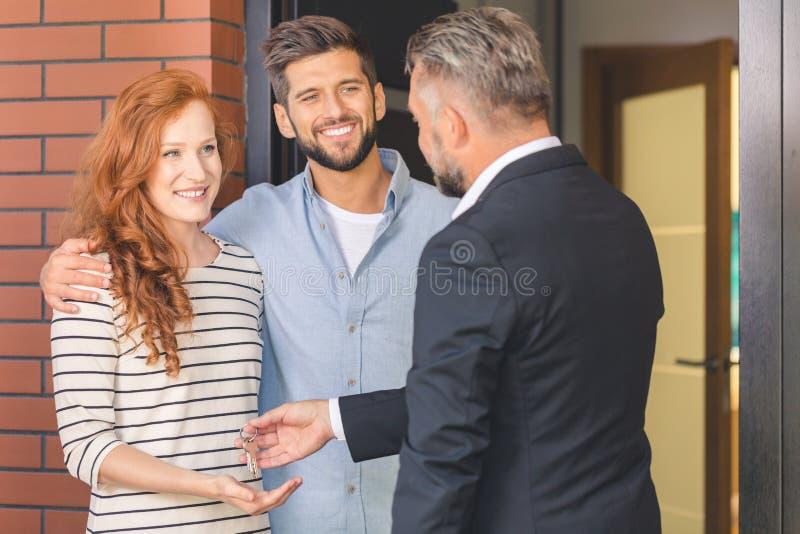 Πράκτορας που δίνει τα κλειδιά στο χαμογελώντας ζεύγος στοκ φωτογραφία με δικαίωμα ελεύθερης χρήσης