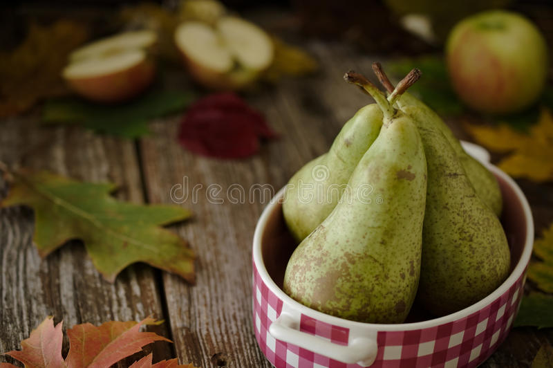 Πράσινα αχλάδια στο ρόδινο πιάτο με τα μήλα στην αγροτική ρύθμιση στοκ φωτογραφία με δικαίωμα ελεύθερης χρήσης