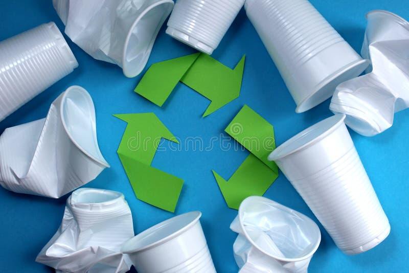 Πράσινα βέλη σύστασης που περιβάλλονται από τα μίας χρήσης πλαστικά άσπρα γυαλιά στοκ φωτογραφίες