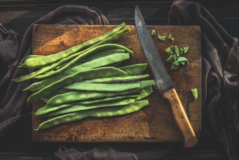 Πράσινα γαλλικά φασόλια στον αγροτικό τέμνοντα πίνακα με το μαχαίρι κουζινών στο σκοτεινό ξύλινο υπόβαθρο, τοπ άποψη στοκ εικόνες