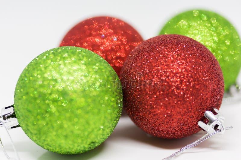 Πράσινα και κόκκινα μπιχλιμπίδια Χριστουγέννων σε ένα άσπρο υπόβαθρο στοκ φωτογραφίες