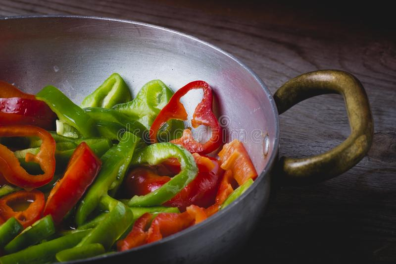Πράσινα και κόκκινα πιπέρια σε ένα τηγάνι στοκ εικόνα