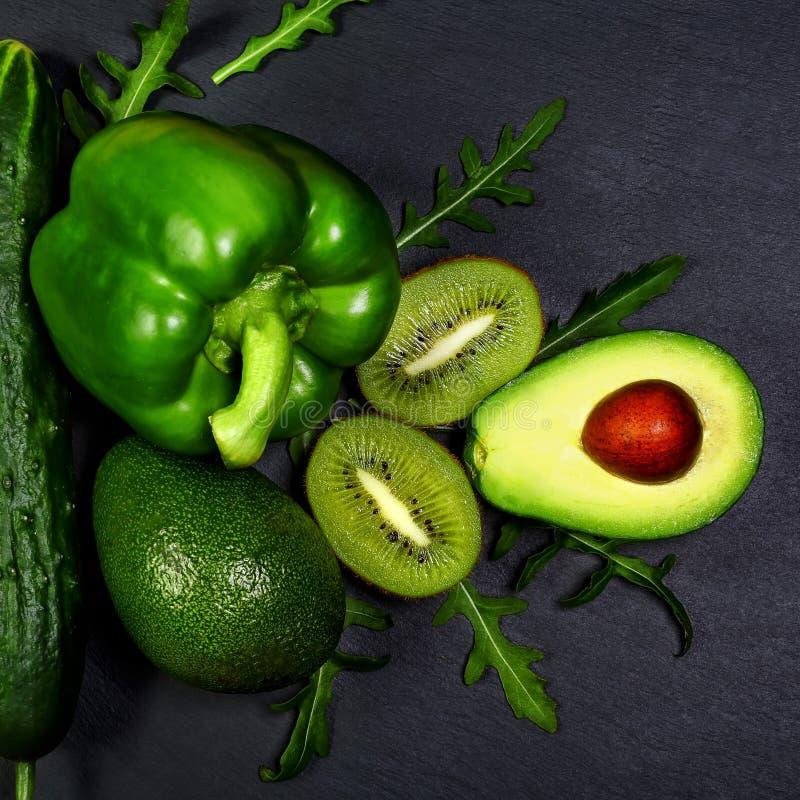 Πράσινα λαχανικά κατατάξεων και φρούτα, αβοκάντο, ακτινίδιο, πιπέρι και αγγούρι, σαλάτα rucola σε έναν πίνακα σχιστόλιθου, η έννο στοκ φωτογραφία με δικαίωμα ελεύθερης χρήσης