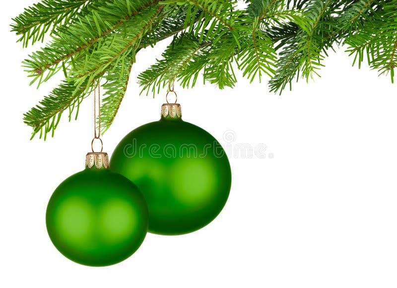Πράσινα μπιχλιμπίδια Χριστουγέννων που κρεμούν από τους φρέσκους πράσινους κλαδίσκους στοκ εικόνες