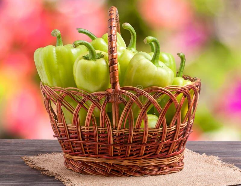 Πράσινα πιπέρια κουδουνιών σε ένα ψάθινο καλάθι στον ξύλινο πίνακα με το θολωμένο υπόβαθρο στοκ φωτογραφία με δικαίωμα ελεύθερης χρήσης