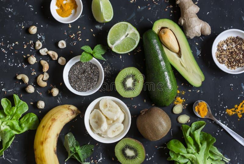 Πράσινα συστατικά καταφερτζήδων Μαγειρεύοντας υγιείς καταφερτζήδες detox Σε μια σκοτεινή ανασκόπηση στοκ φωτογραφία