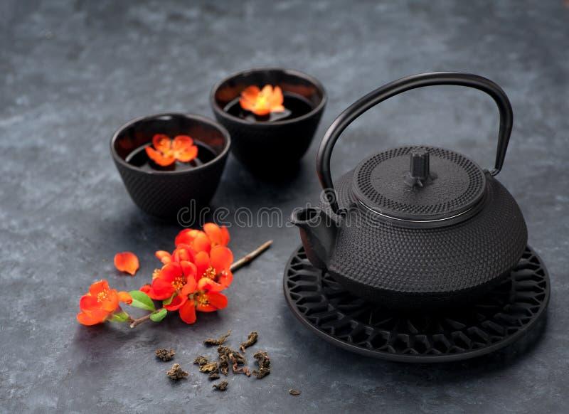 Πράσινα τσάι και λουλούδια Μαύρα teapot και φλυτζάνια ύφους σιδήρου ασιατικά στοκ φωτογραφία με δικαίωμα ελεύθερης χρήσης