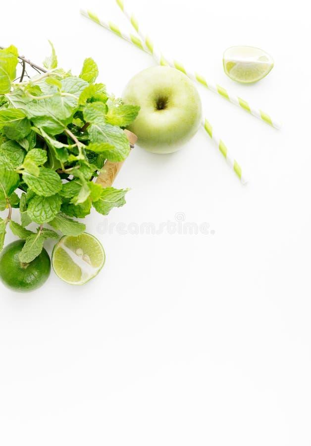 Πράσινα υγιή συστατικά ποτών στο άσπρο υπόβαθρο: ασβέστης, μήλο, φρέσκια μέντα και ζωηρόχρωμα άχυρα εγγράφου Χορτοφάγα τρόφιμα de στοκ εικόνες