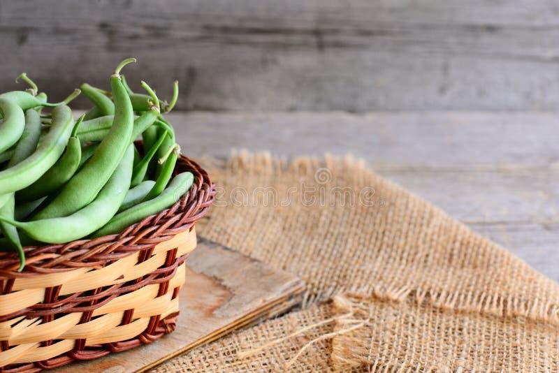Πράσινα φασόλια σειράς σε ένα καφετί καλάθι και σε ένα burlap κλωστοϋφαντουργικό προϊόν Φυσικοί νέοι λοβοί φασολιών παλαιός ξύλιν στοκ εικόνα