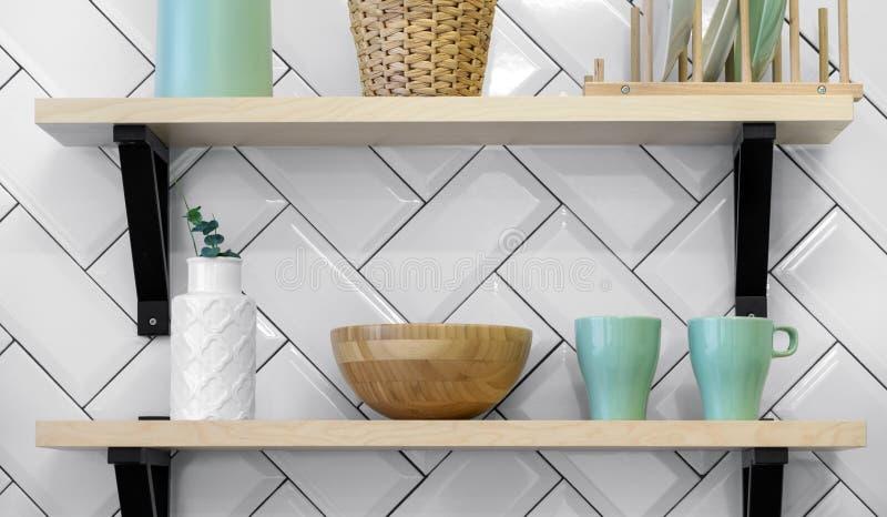 Πράσινα φλυτζάνια σκευών για την κουζίνα και άσπρο βάζο στα ξύλινα ράφια στοκ εικόνες