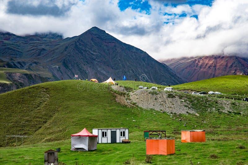 Πράσινα χλόη θερινών βουνών και τοπίο μπλε ουρανού Στρατόπεδο τουριστών Σκοτεινές αιχμές Μια μεγάλη θέση που χαλαρώνει Gudauri στοκ φωτογραφία με δικαίωμα ελεύθερης χρήσης