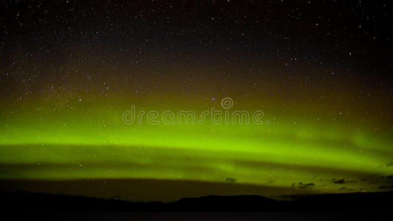 Πράσινες βόρειες φω'τα και μυριάδα των αστεριών στοκ φωτογραφίες