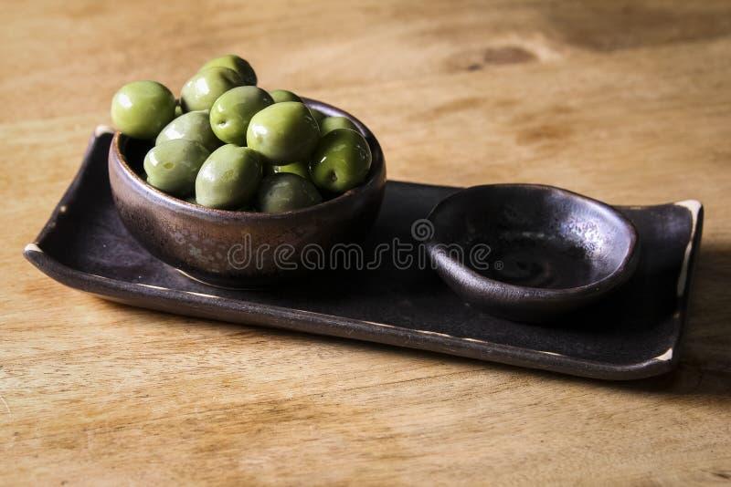 Πράσινες ελιές σε ένα κεραμικό κύπελλο σε ένα ξύλινο υπόβαθρο στοκ φωτογραφίες