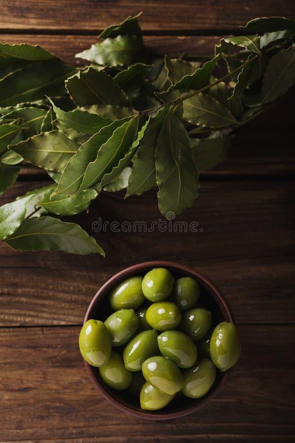Πράσινες ελιές σε ένα κεραμικό κύπελλο σε ένα ξύλινο υπόβαθρο στοκ φωτογραφία με δικαίωμα ελεύθερης χρήσης