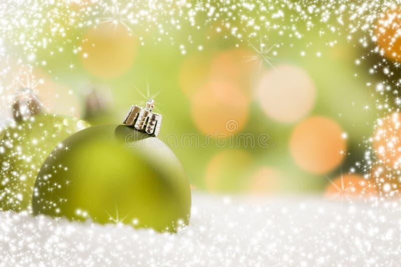 Πράσινες διακοσμήσεις Χριστουγέννων στο χιόνι πέρα από ένα αφηρημένο υπόβαθρο στοκ εικόνες