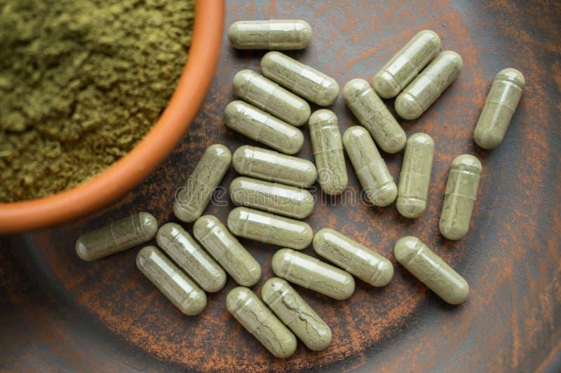 Πράσινες κάψες και σκόνη συμπληρωμάτων kratom στο καφετί πιάτο χορτάρι στοκ φωτογραφίες