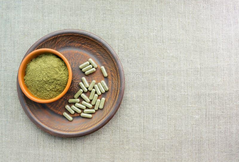 Πράσινες κάψες και σκόνη συμπληρωμάτων kratom στο καφετί πιάτο χορτάρι στοκ εικόνα