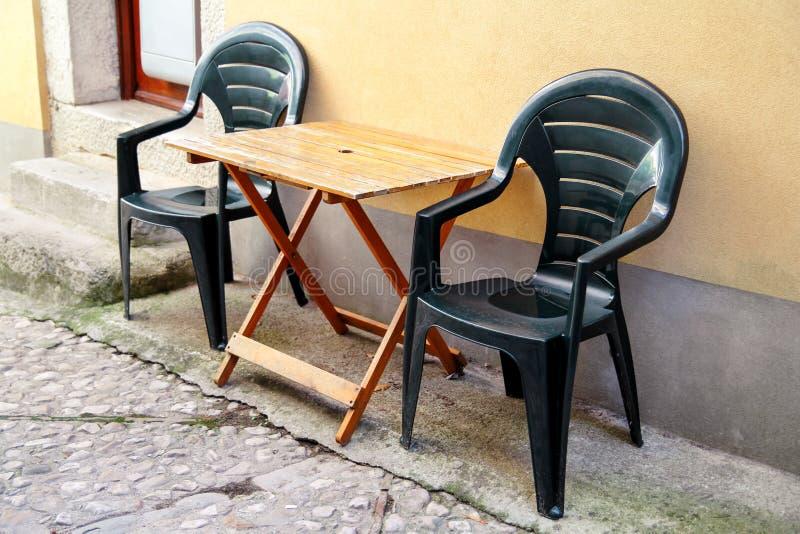 Πράσινες πλαστικές καρέκλες και ξύλινος πίνακας υπαίθριοι μπροστά από το σπίτι στο πεζούλι και την οδό/τη ρύθμιση του γραφείου κα στοκ εικόνα με δικαίωμα ελεύθερης χρήσης