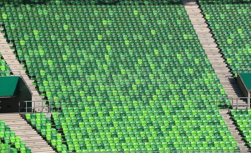 Πράσινες πλαστικές καρέκλες σταδίων στους λευκαντές στη σειρά στοκ εικόνα με δικαίωμα ελεύθερης χρήσης