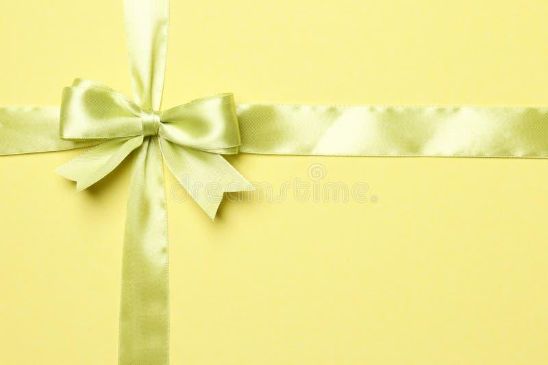 Πράσινες τόξο και κορδέλλα Ight που απομονώνονται στο κίτρινο υπόβαθρο στοκ φωτογραφία με δικαίωμα ελεύθερης χρήσης