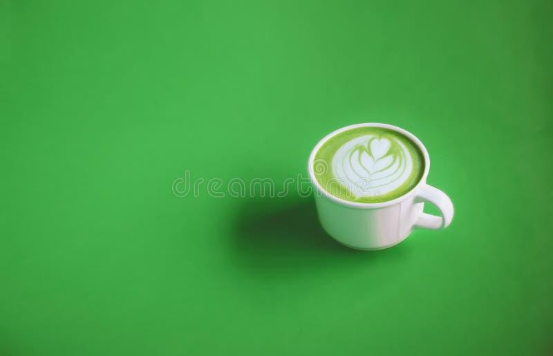 Πράσινη έννοια τσαγιού, πράσινο γάλα τσαγιού με την τέχνη στην κορυφή με το άσπρο φλυτζάνι στο πράσινο υπόβαθρο για το έμβλημα στοκ εικόνες με δικαίωμα ελεύθερης χρήσης