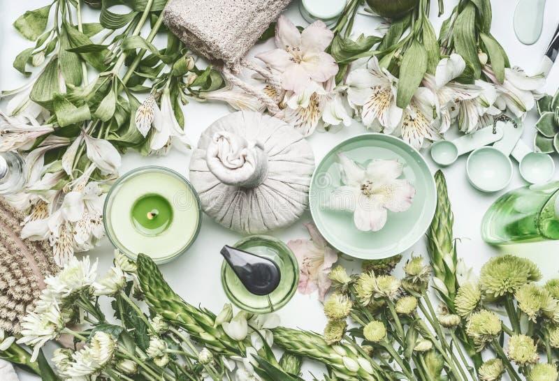 Πράσινη βοτανική SPA που θέτει με το κύπελλο νερού, τα λουλούδια, το κερί, τις σφαίρες μασάζ, τα καλλυντικά προϊόντα, τα χορτάρια στοκ φωτογραφία