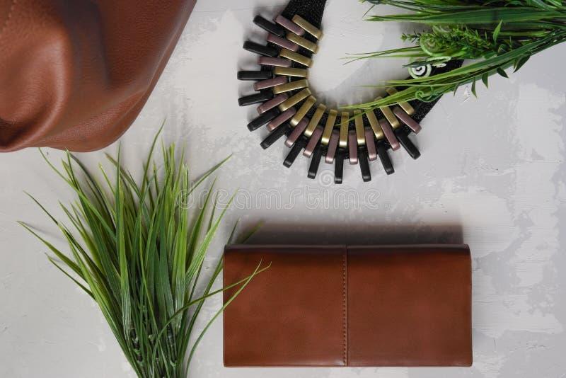 Πράσινη δέσμη της χλόης στο υπόβαθρο του περιδεραίου και του καφετιού πορτοφολιού στοκ φωτογραφίες με δικαίωμα ελεύθερης χρήσης