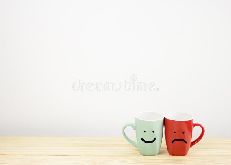 Πράσινη και κόκκινη κούπα καφέ με το χαμόγελο και λυπημένο πρόσωπο στον ξύλινο πίνακα στοκ εικόνες